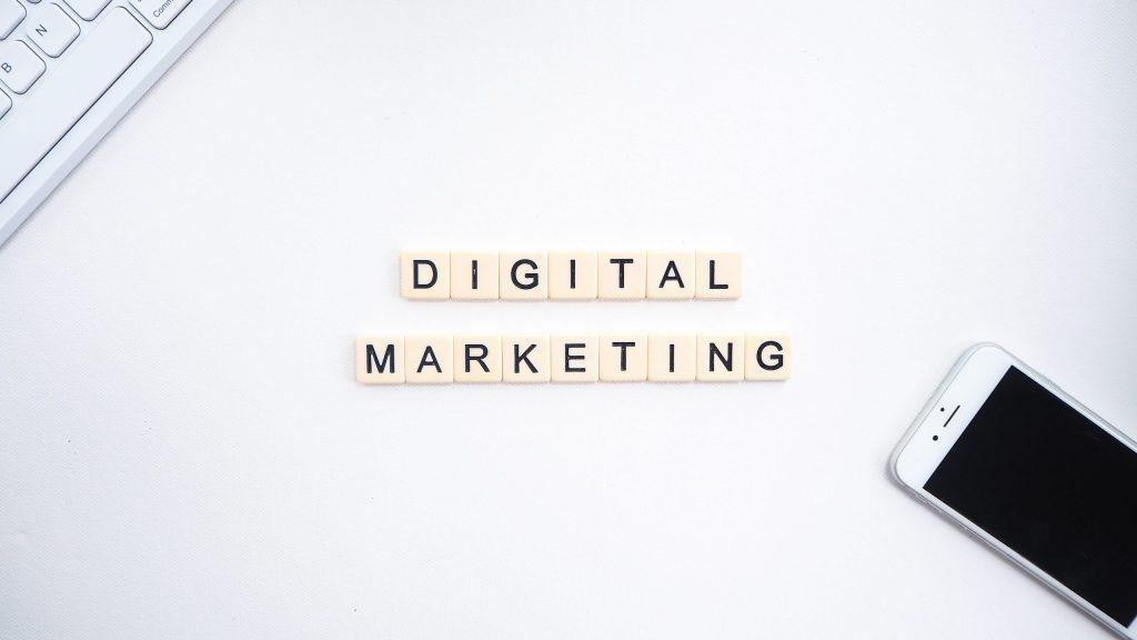 scrivania bianca con telefono e scritta digital marketing
